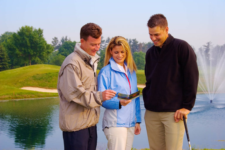 two pro golfers with female model wearing golf apparel for catalogue shoot