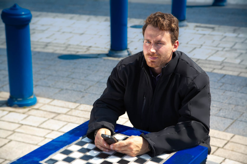 Location Coat - Male Model Seated at Public Chess Table