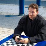 male model at chess board wearing black coat