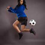 female model jumping with soccer ball kick